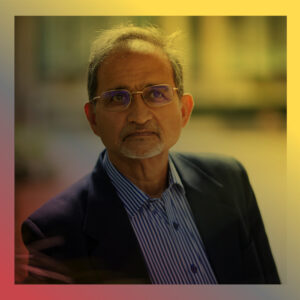 Shekhar Saxena wearing a suit coat and blue and white vertically striped button down, looks slightly off camera. A gradient overlay is over the photo, starting with a bright red-pink on the bottom left, transforming to grey in the middle and bright yellow on the upper left.