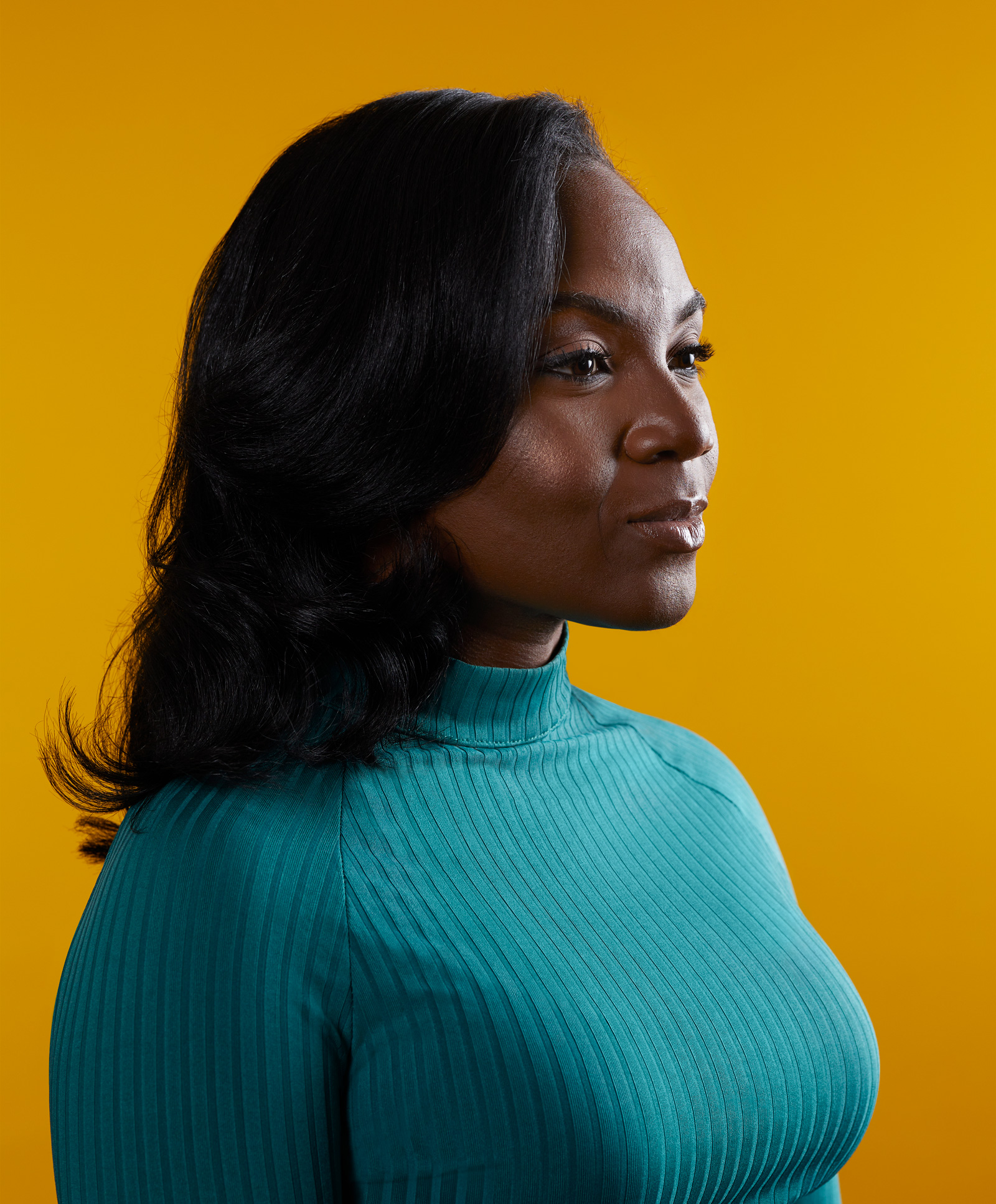 Kizzmekia Corbett wearing a longsleeve, teal turtleneck dress, looks off camera with a serious and powerful expression.