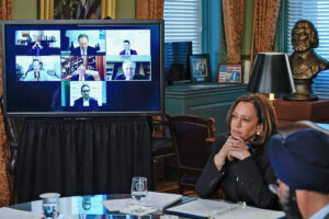 Vice President Harris sits at a table , looking at a large tv screen on her left. Seven people are indivudally shown in a grid for the group zoom call on the screen.
