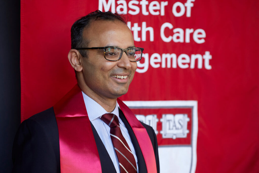 """Male student wearing a suit, crimson tie, and crismon graduation sash poses in front of """"Master of Health Care Management"""" banner"""