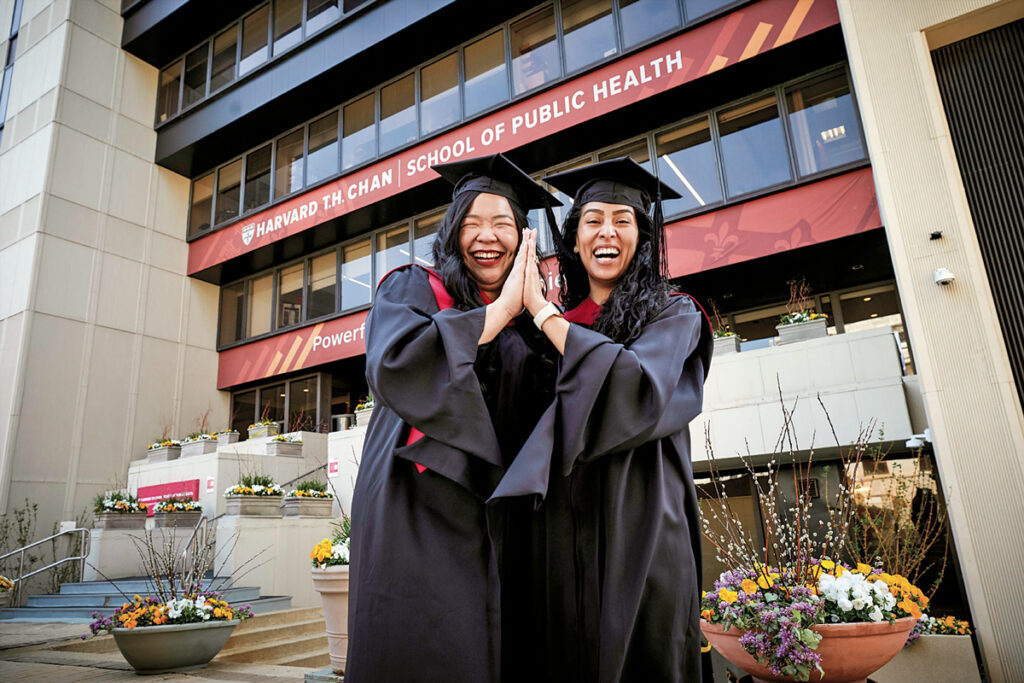 Two female students dressed in graduation robes and hats high five in front of Kresge building.