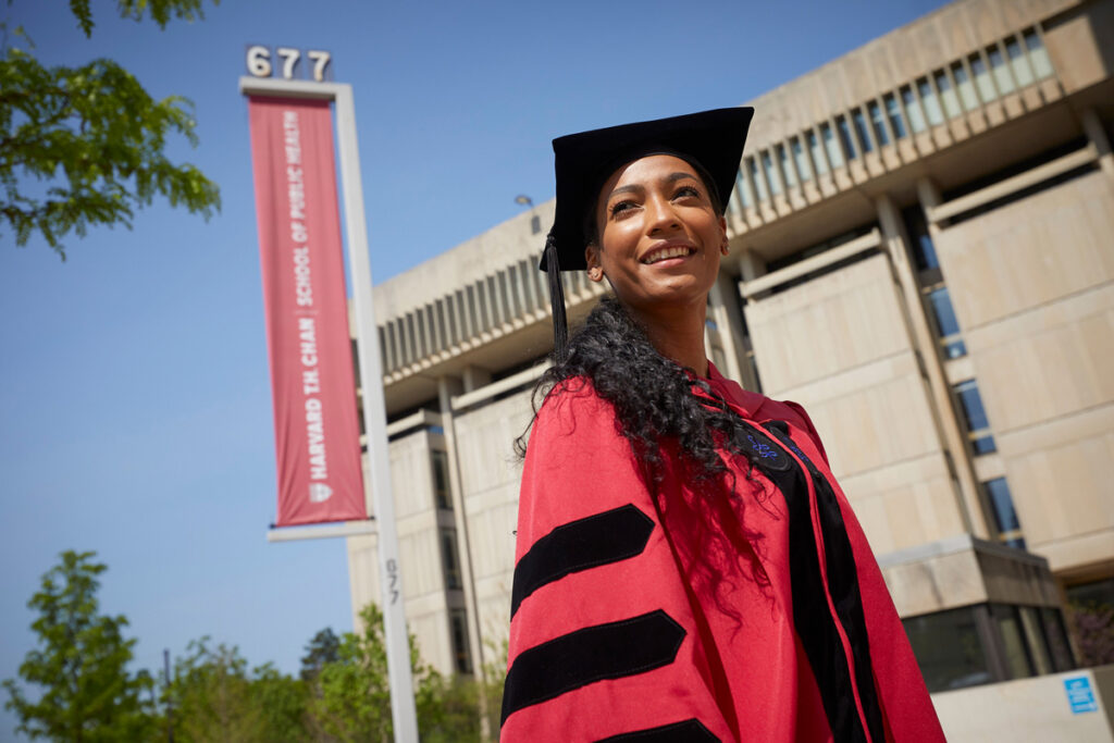 Female student poses outside the Conway Library in Crimson regalia. Harvard T.H. Chan School Banner is in background.