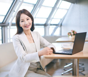 Jane Jie Sun seated at a row of white bench seating, wears a white pant suit with an open laptop beside her, smiling at the camera with her hands rested on the table. The room has large windows and natural light shines around her.