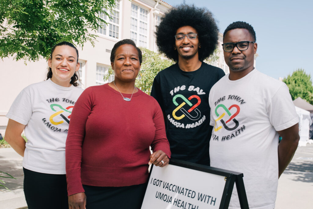 Kim Rhoads stands with three memebers of her team, one female, two male. They wear Umoja Health logo t shirts. Rhoads wheres a long sleeve crimson shirt and a silver necklace.