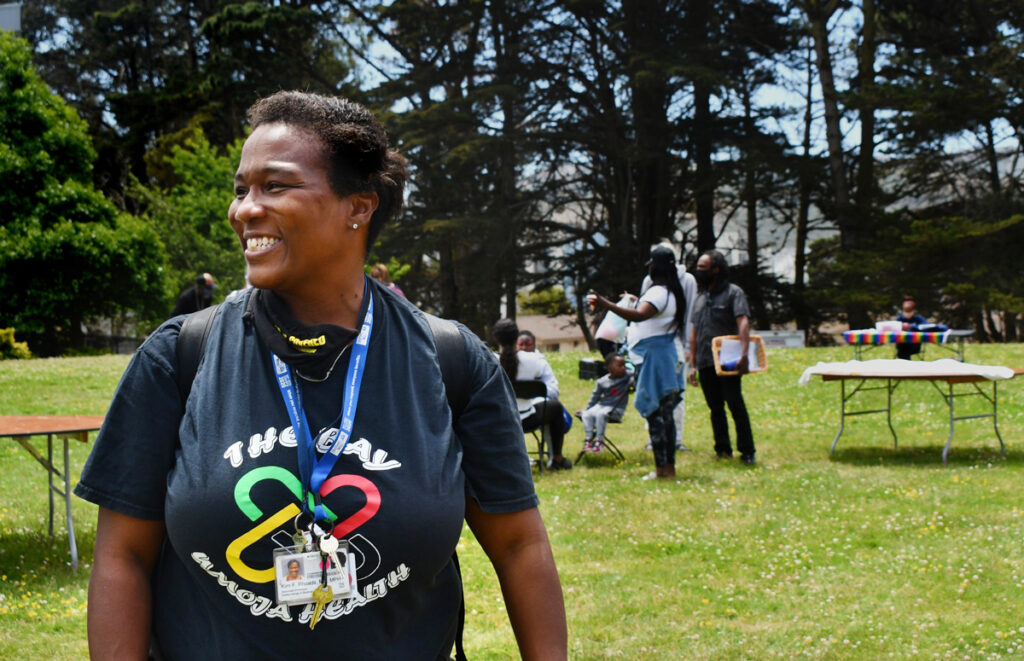 Rhoads wears a black Umoja Health t-shirt outside at a community event in a park. She smiles at something off camera left.