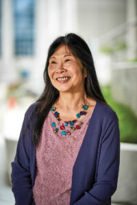 Professor Phyllis Kanki stands outside on a concrete walkway with greenery behind her. She wears a purple cardigan, light pink shirt and colorful beaded necklace. She has black hair that extends past her shoulders and a natural smile.