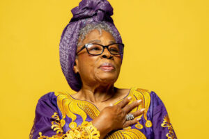 Opal Lee wears a purple and gold dress and headscarf, with one hand over her heart.