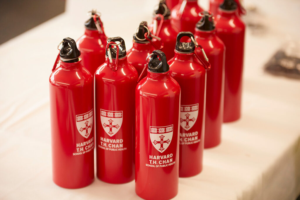 Collection of metal red Harvard Chan water bottles with black tops with red carribeaners sit on a white table.