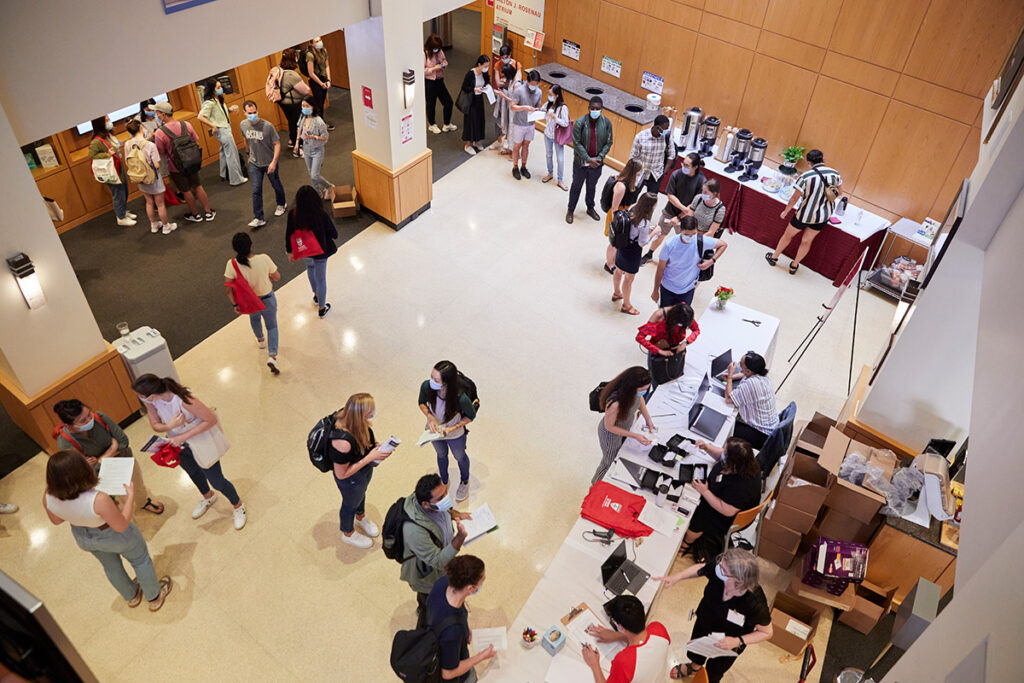 Birds-eye view of orientation in the Kresge lobby. Students stand in line watiing to recieve orientation materials. Others stand in small groups.