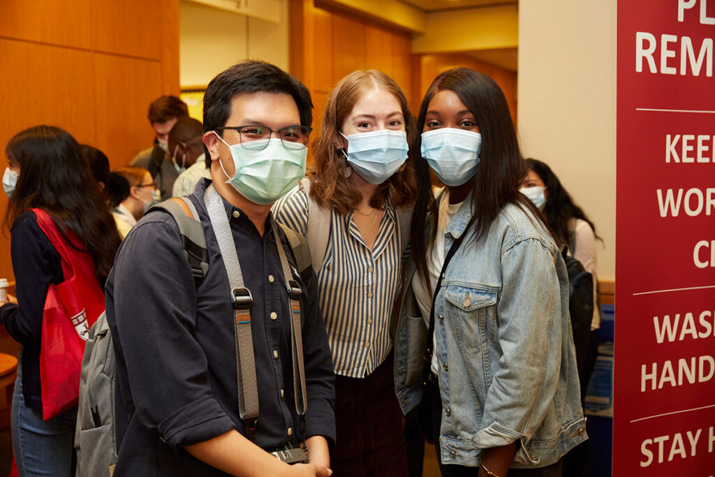 Three masked students pose for the camera in Kresge during orientation.