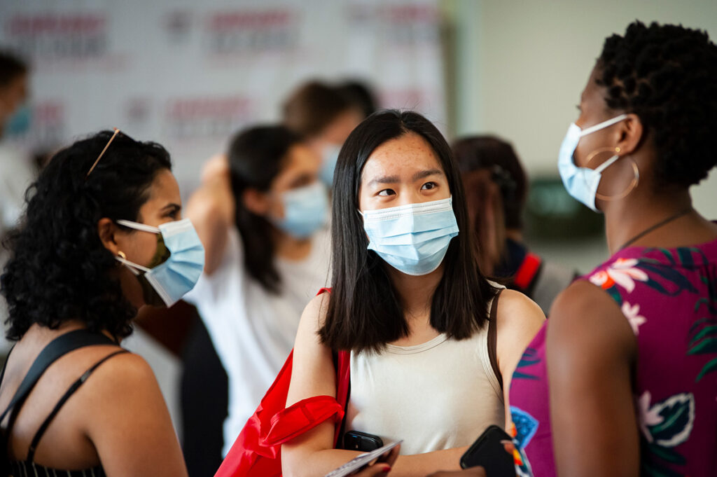 Three masked female students converse at orientation.
