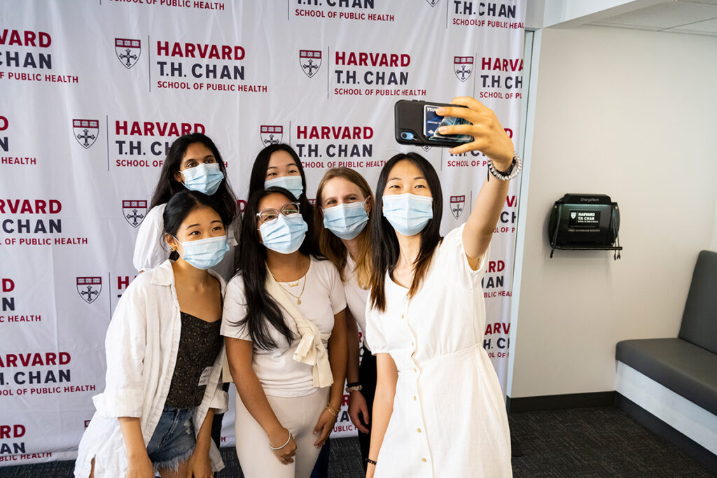 Six masked female students take a selfie in front of a photo backdrop with the Harvard Chan logo repeated.