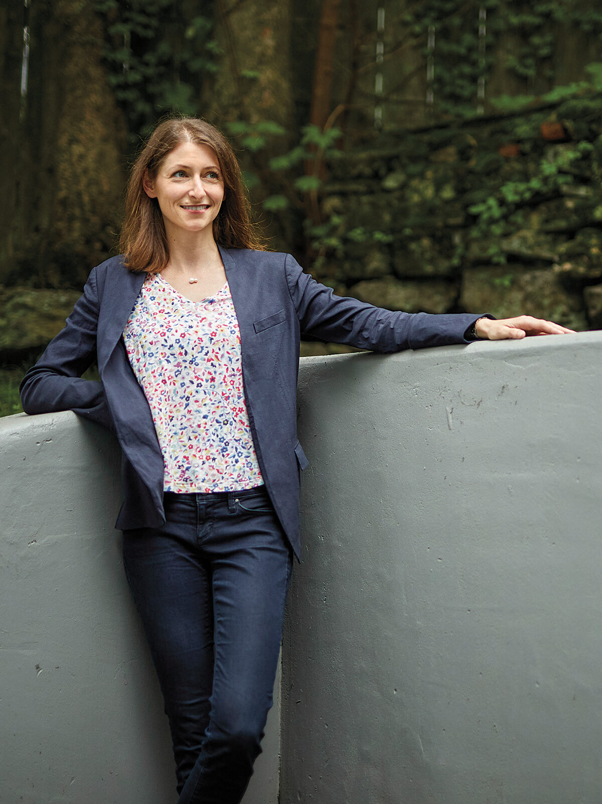 Nora Kory stands in a wooded area by a short concrete wall, resting one elbow on one side, and extending her arm on the other. She wears jeans, a multicolored shirt and a dark blue blazer.