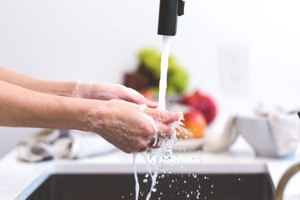 washing hands at a sink with color fruits and vegetables in the counter on the background