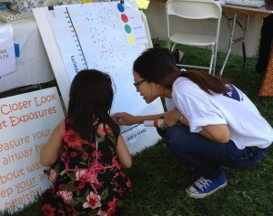 Two girls at the Hoops and Health event plot their airway health results on our peak flow graphs.