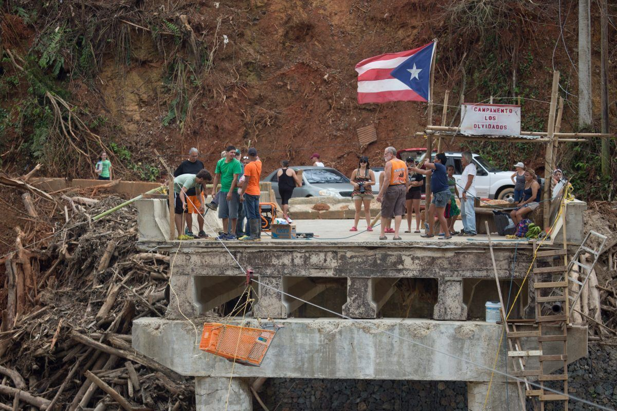 Utuado, Puerto Rico -- Villagers collect on bridge remnants to receive needed supplies. The village has been cut-off by the Rio Charco Abajo's flooding that took away the village road and bridge. An ingenious cable pulley system ferries a shopping cart from shore-to-shore.