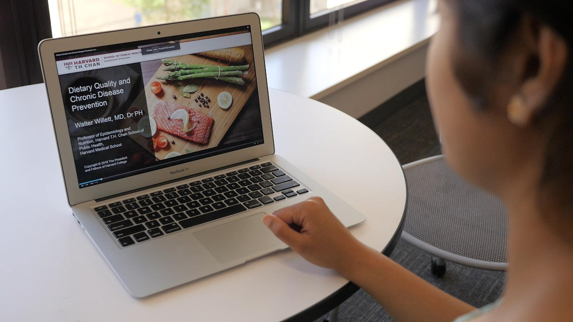 A woman sitting at a laptop taking an online nutrition course