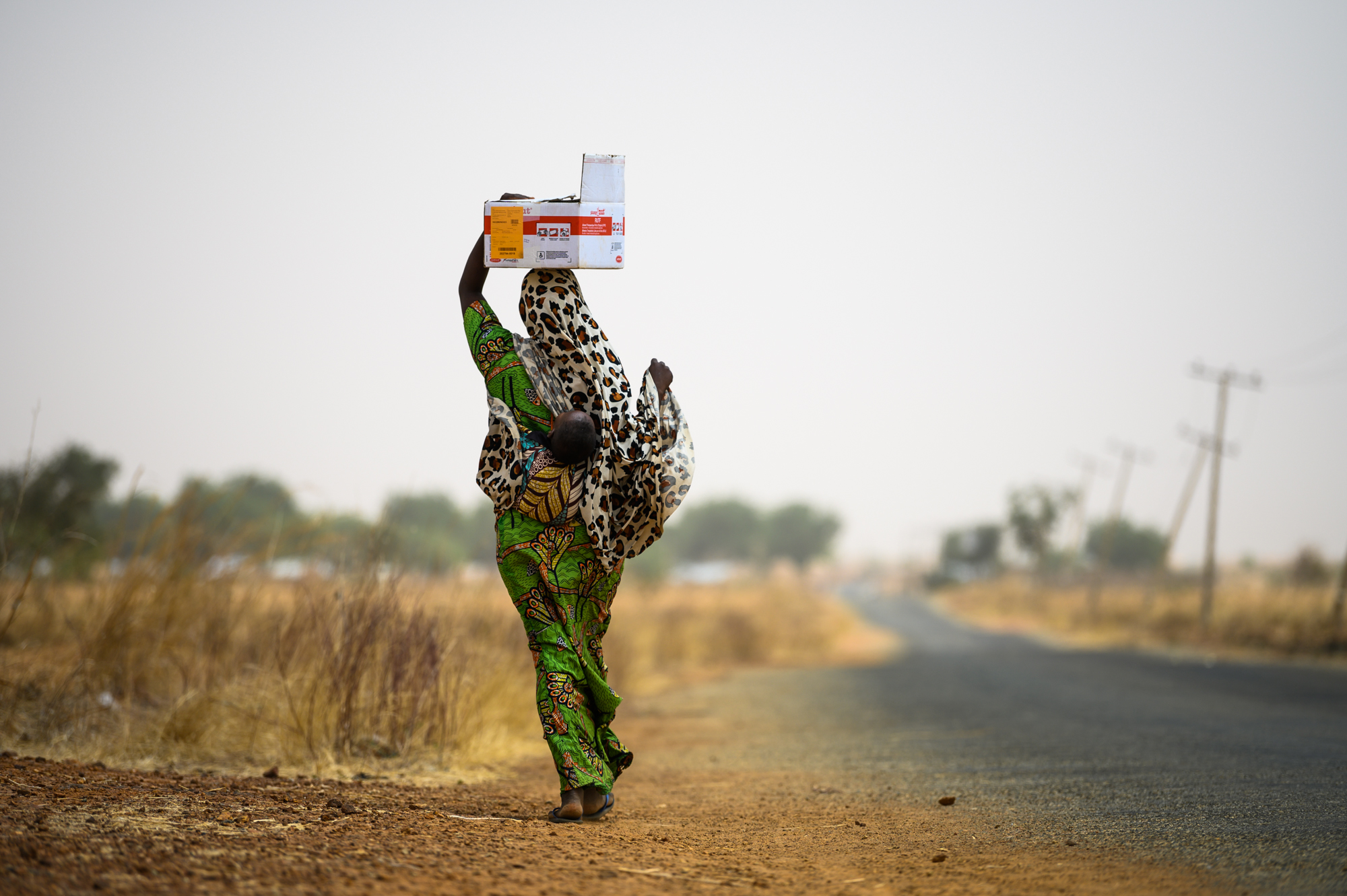 a mother carries her child on her back while carrying a box of food packets in Sokoto Nigeria