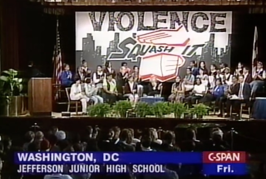 "Shot of stage with ""Squash It!"" Campaign banner and students, Harvard-MetLife Leadership Forum (May 16, 1997, featuring First Lady Hillary Clinton)"