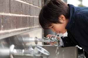boy_drinking_from_fountain_outside_of_a_school