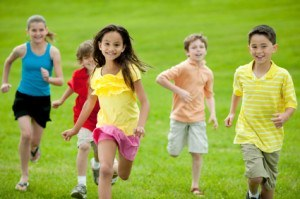 Kids of varying ages running through a field