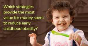 Little girl holding a spoon - The text says: Which strategies provide the most value for money spent to reduce early childhood obesity?