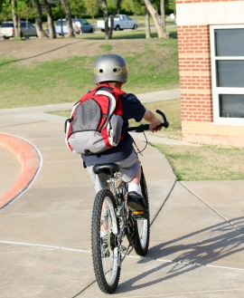 A boy riding home from school on his bike.